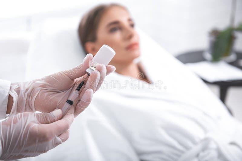 Шприц Cosmetologist заполняя пока молодая дама лежа на кушетке стоковое изображение rf