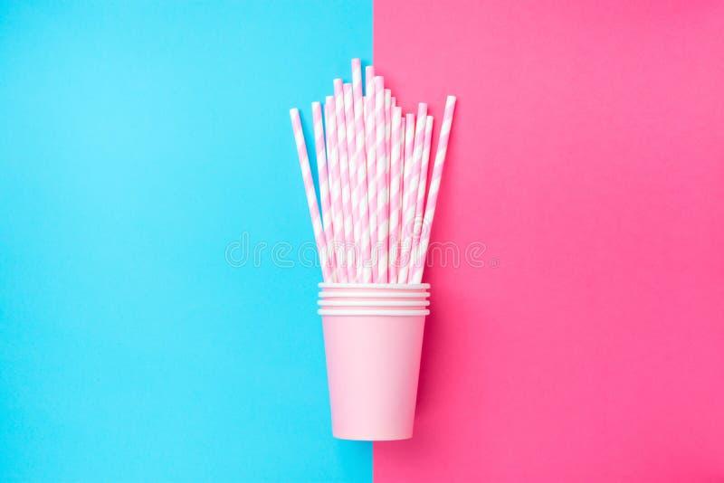 Штабелированные выпивая бумажные стаканчики с Striped соломами на тоне дуо чеканят голубую розовую предпосылку Плоское положение  стоковое фото rf
