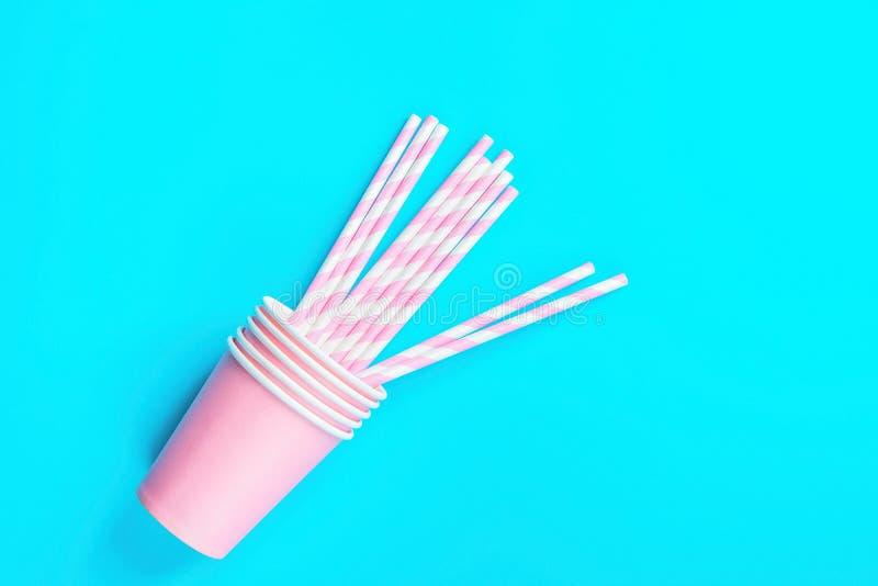 Штабелированные выпивая бумажные стаканчики Striped соломы на свете - голубой предпосылке Плоский состав положения Торжество вече стоковые фото
