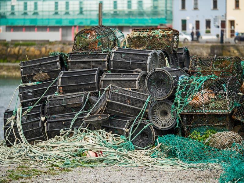 Штабелированные пустые ловушки рыб, выборочный фокус, таунхаусы на заднем плане стоковое фото