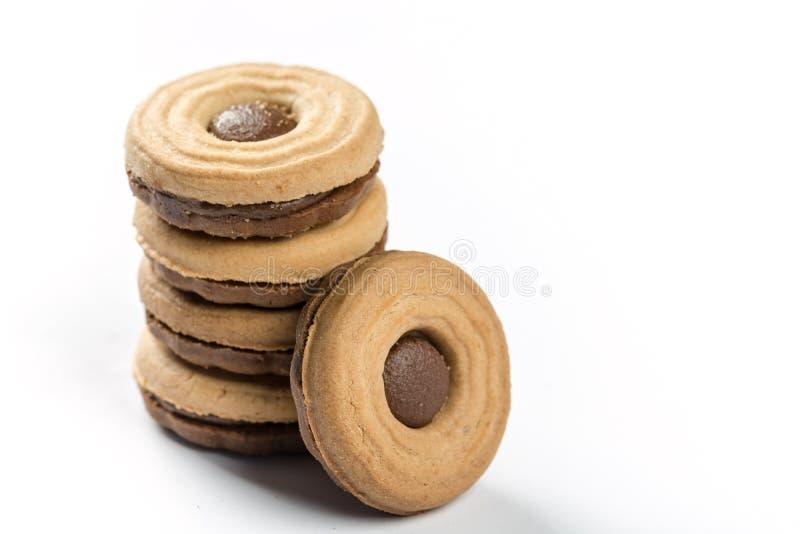 Штабелированный вокруг печениь покрыл с сливк шоколада над белой предпосылкой стоковые изображения