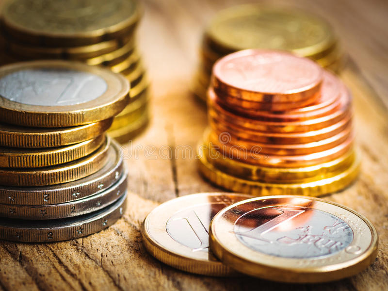 Штабелированные сияющие белые и золотые монетки различного значения на деревянной предпосылке, финансы евро, вклад, запас, концеп стоковые фотографии rf