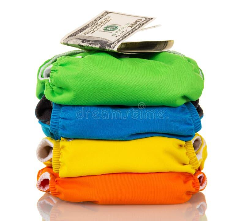 Штабелируйте современные пеленки и доллары ткани изолированные на белой предпосылке стоковые изображения rf