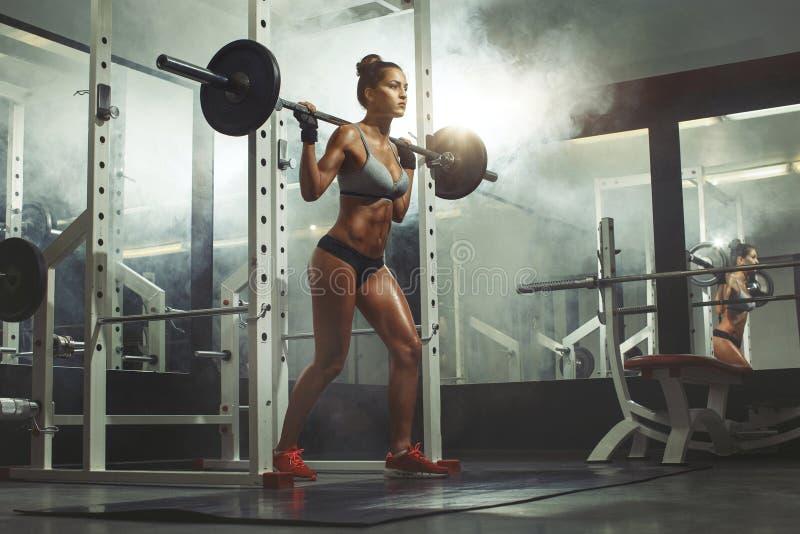 Штанга женщины поднимаясь с весом в спортзале стоковое изображение