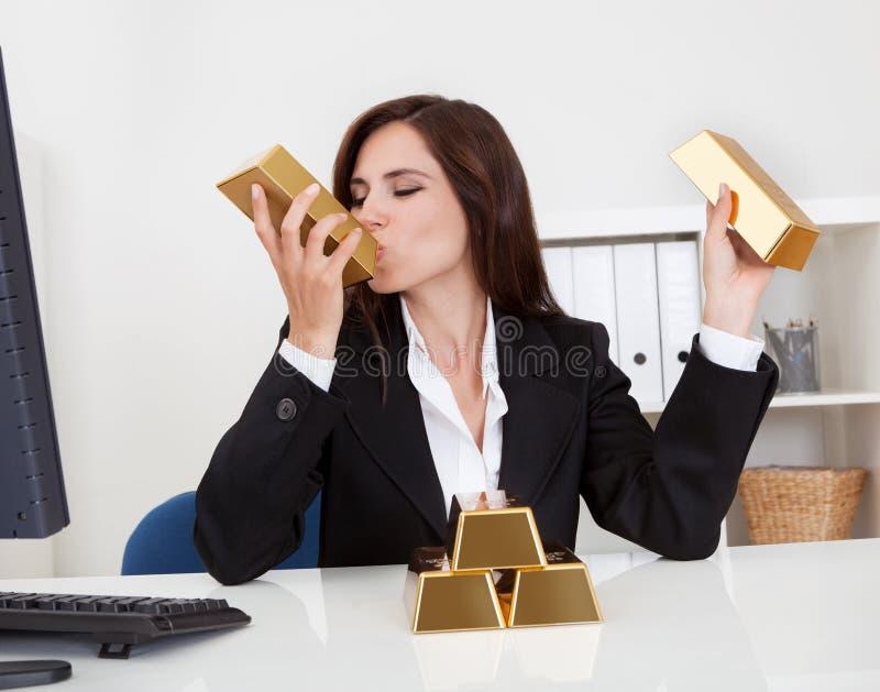 Штанга золота удерживания коммерсантки стоковая фотография rf