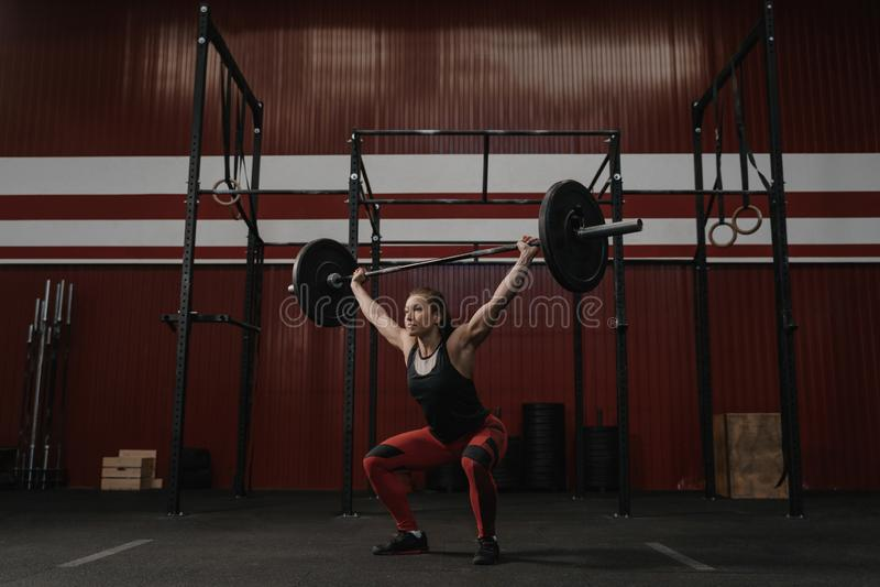 Штанга сильной женщины поднимаясь наверху, делающ тренировки crossfit стоковое изображение rf