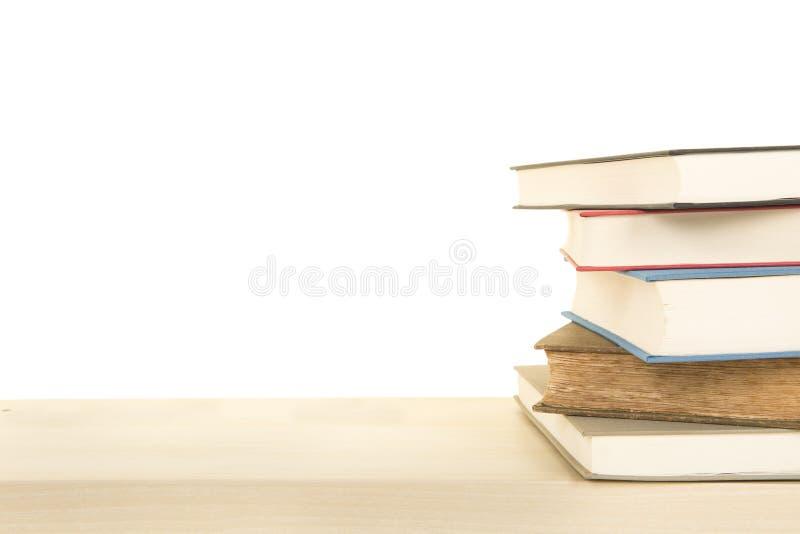 Штапель книг лежа вниз на деревянной полке на белой предпосылке с космосом для экземпляра стоковые фото