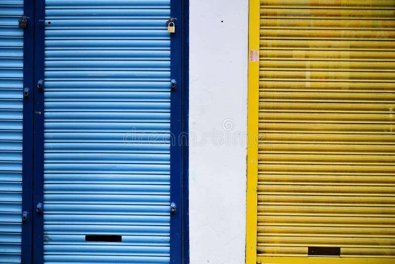 Штарки магазинов закрыли желтый цвет и синь стоковое изображение