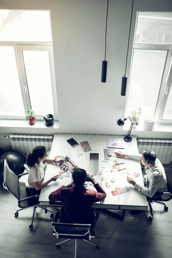 Штат журнала сидя на таблице и имея обсуждение стоковое изображение