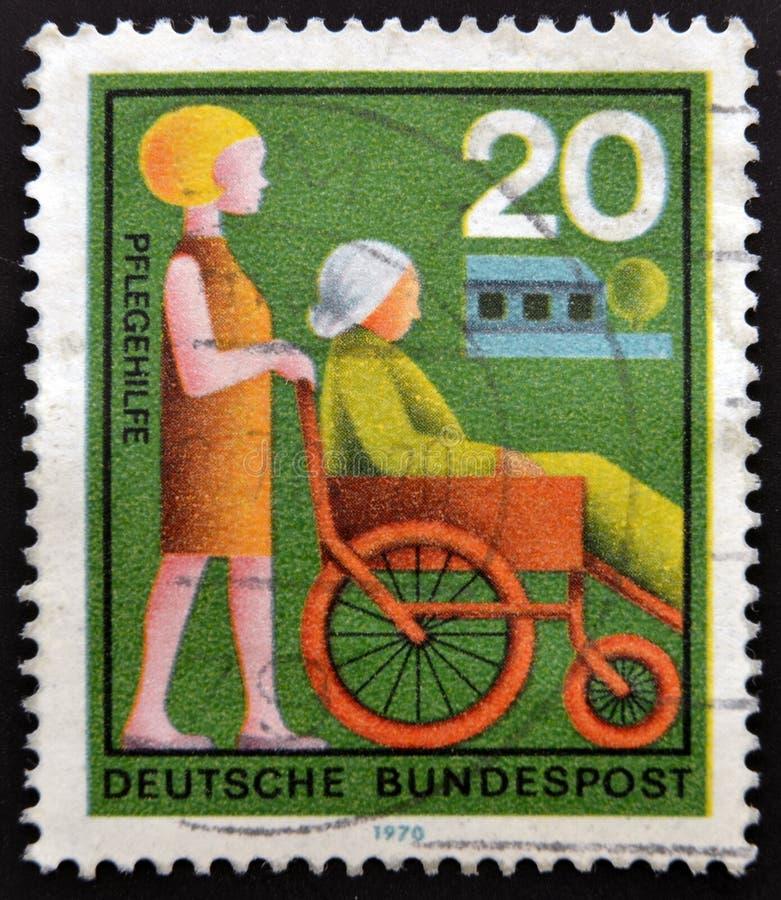 Штемпель напечатанный в Германии показывает помощь женщины стоковое изображение