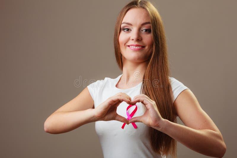 штемпель фондом находки дракой лечения рака молочной железы почтовый Женщина делая форму сердца на розовой ленте стоковые изображения rf