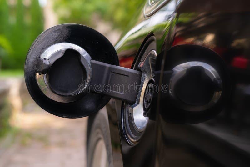 Штепсельная вилка заряжателя в электрический автомобиль в зеленой предпосылке окружающей среды Новый корабль энергии, NEV нагружа стоковое фото