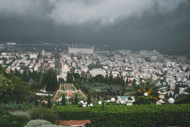 Шторм дождя и тяжелые облака над центром города Хайфы, взглядом с морским портом, гаванью Хайфы, индустриальной зоной, садами Bah стоковые фотографии rf
