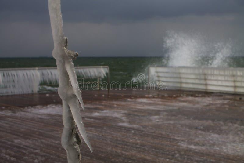 Шторм зимы покрывает кабели на набережной с сосульками стоковое изображение