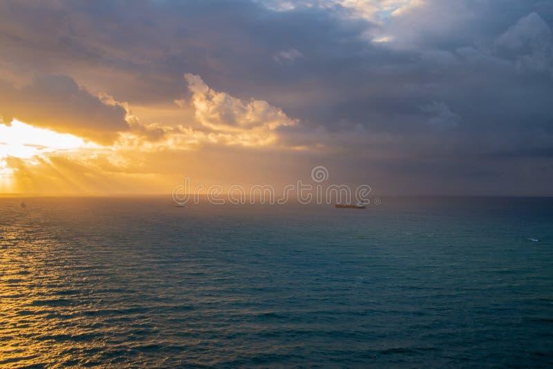 Шторм с толстыми темными облаками причаливая побережью на восходе солнца Световые лучи приходят от солнца thew за темными облакам стоковые изображения
