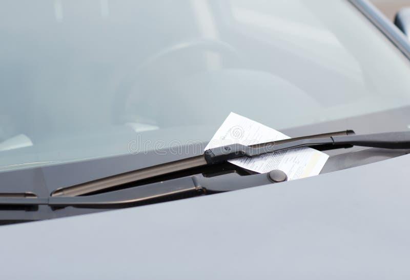 Штраф за нарушение правил стоянки на windscreen автомобиля стоковые изображения rf