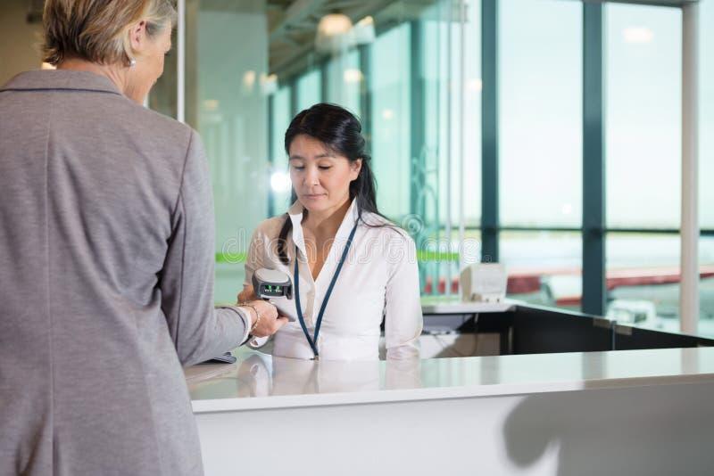 Штрихкод скеннирования работник службы рисепшн авиапорта на мобильном телефоне, который держит бушель стоковое фото rf