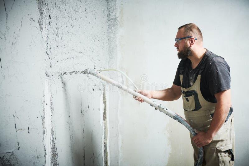 Штукатур используя миномет гипсолита замазки screeder распыляя на стене стоковая фотография rf