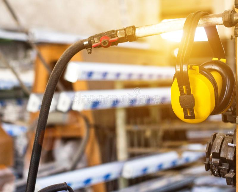 Шум на рабочем месте, желтые наушники безопасности против вида шума в мастерской для изготовления окон PVC стоковые изображения
