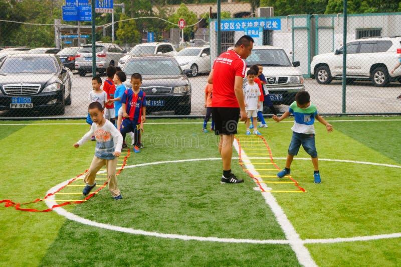 Шэньчжэнь, Китай: Основные умения детей в тренировке футбола стоковое изображение