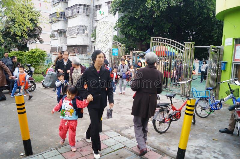 Шэньчжэнь, Китай: через после полудня детского сада после школы, родителей принимает их детей домой стоковое фото