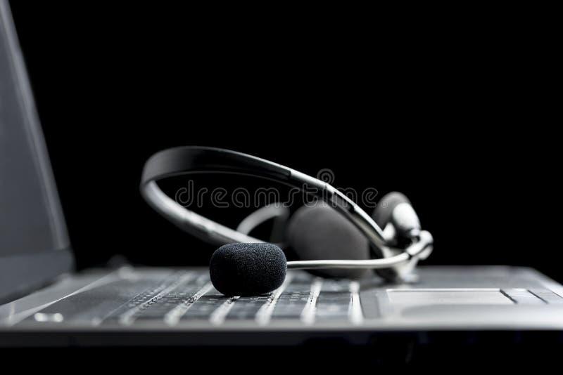 Шлемофон лежа на портативном компьютере стоковая фотография rf