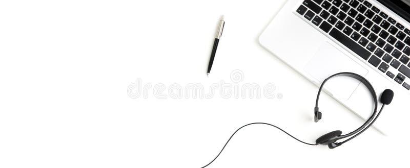 Шлемофон микрофона с компьютер-книжкой и ручка на белой таблице стоковая фотография rf