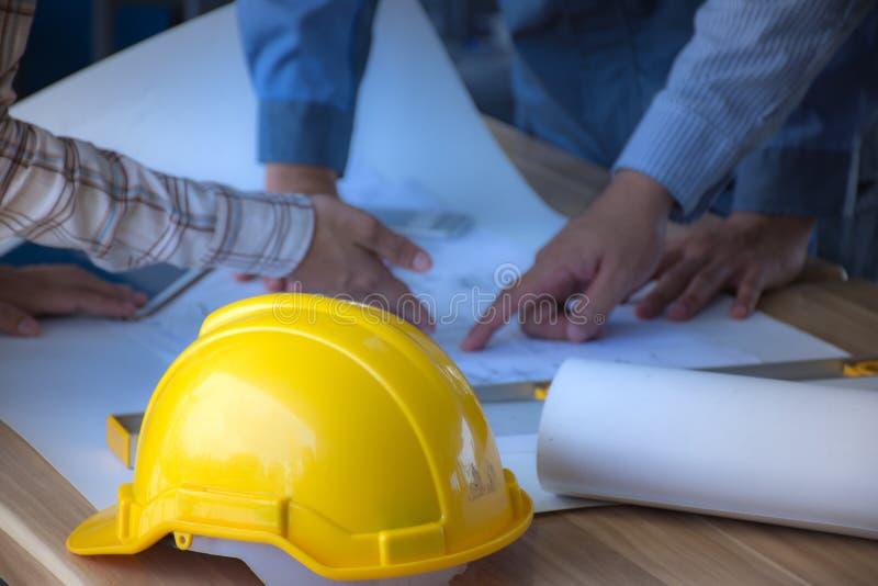 Шлем безопасности помещенный на команде инженерства таблицы встречи шлем фокуса /Selective на предохранительном взводе стоковые изображения rf