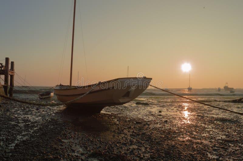 Шлюпка во время отлива на заходе солнца стоковое изображение rf
