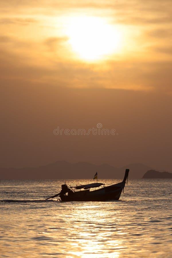Шлюпка глубины поля сиротливая на пляже на времени захода солнца стоковые фото