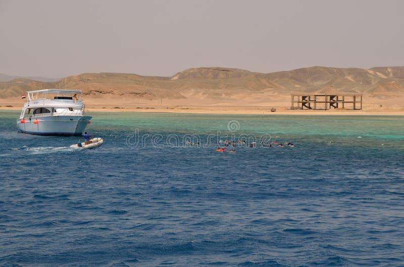 Шлюпка и много snorkelers в море стоковое фото rf