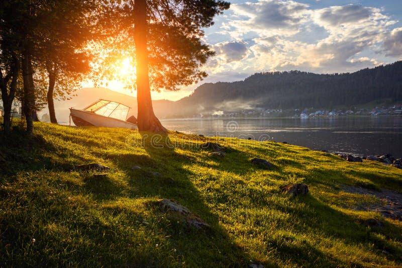 Шлюпка на озере на предпосылке захода солнца в ясном летнем дне Теплый вечер лета на доке около шлюпки Фантастичные взгляды стоковое фото