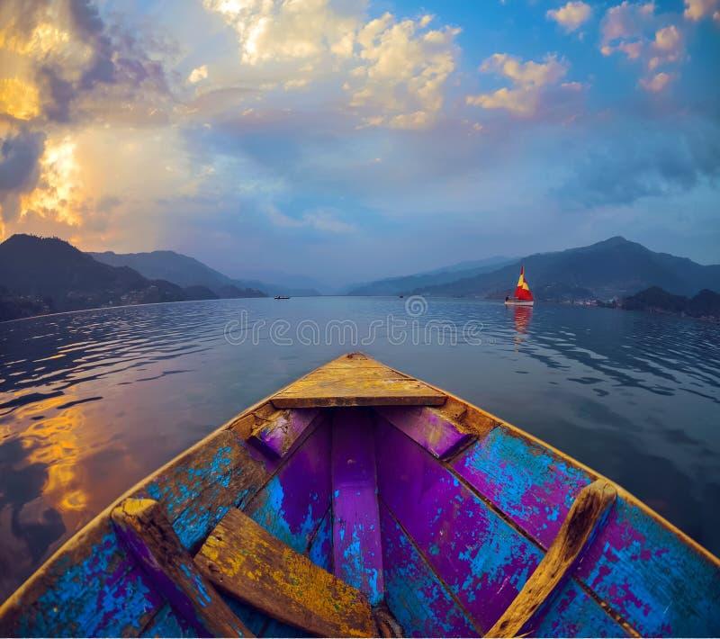 Шлюпка на озере Fewa, ландшафт с горами Гималаев и облака стоковые изображения