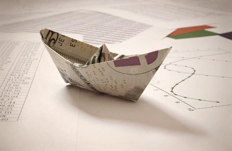 Шлюпка доллара бумажная на финансовых данных стоковая фотография