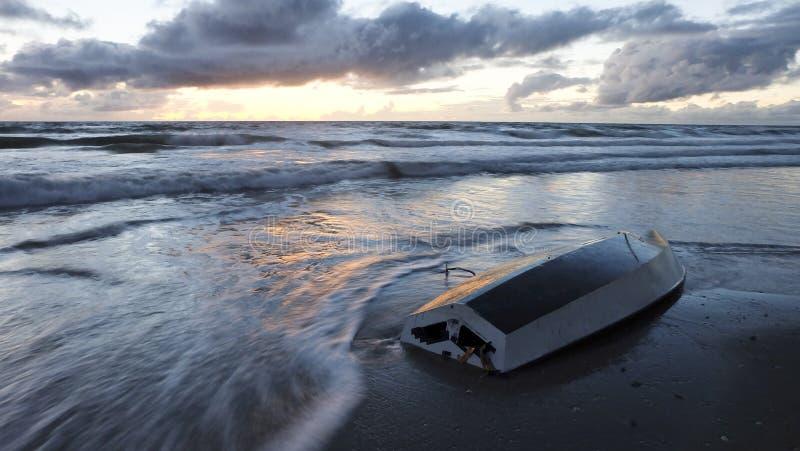 Шлюпка приставанная к берегу восходом солнца стоковые фотографии rf