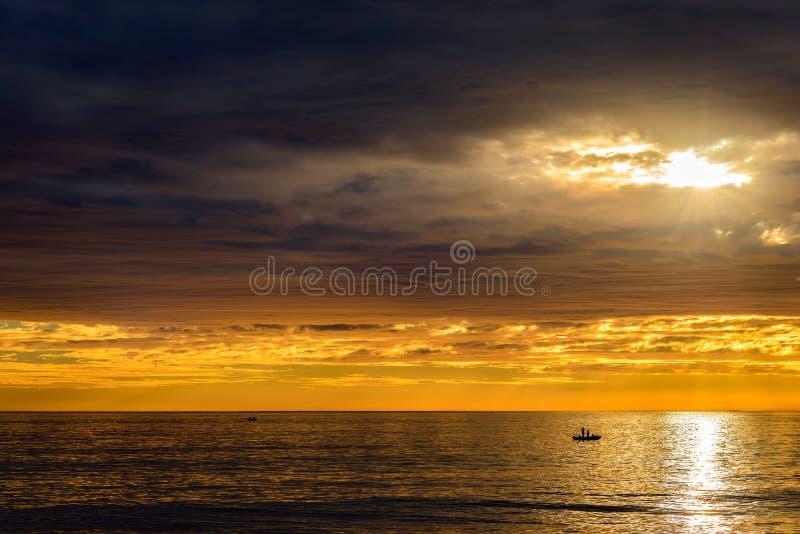 Шлюпка с рыболовами на заходе солнца стоковое фото