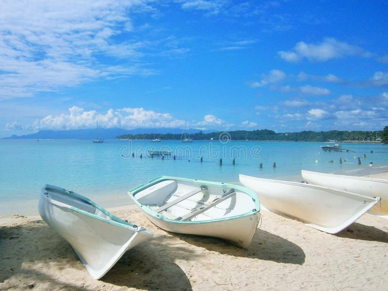 Шлюпки, лежа на белом песчаном пляже на Гваделупе в Вест-Инди стоковые изображения