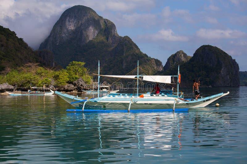 Шлюпки ждать туристов для того чтобы путешествовать между островами El Nido, Филиппиныы стоковая фотография rf
