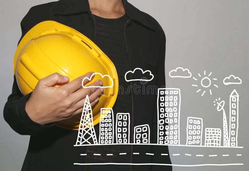 шляпа и рука безопасности желтого цвета владением бизнес-леди нарисованные skyscrap стоковая фотография rf