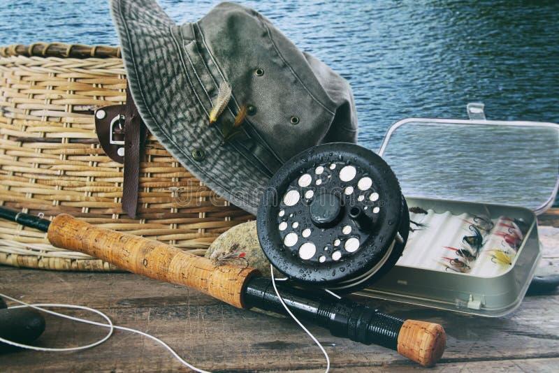 Шляпа и рыболовные принадлежности мухы на таблице около воды стоковое фото rf