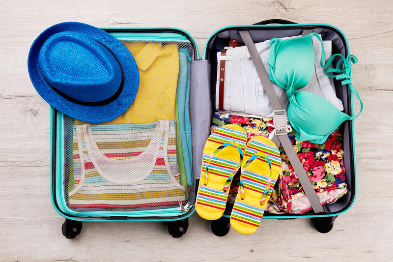 Шляпа и тапочки на упакованном чемодане стоковое фото rf