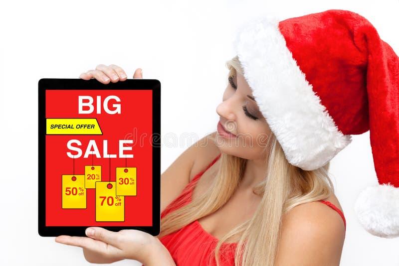 Шляпа рождества женщины красная держа планшет с большой продажей стоковые фотографии rf