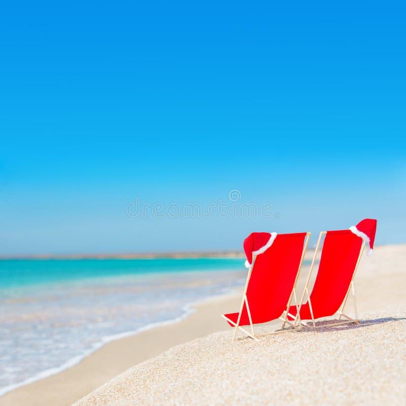 Шляпа Санты на шезлонгах на пляже с белым песком против моря стоковое фото