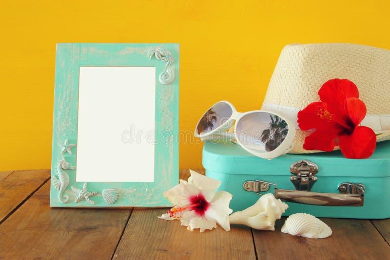 Шляпа Fedora, солнечные очки, тропический гибискус цветет рядом с пустой рамкой над деревянным столом стоковые изображения
