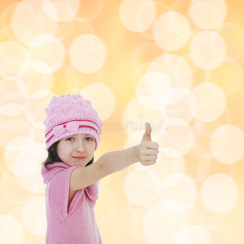 Шляпы связанные маленькой девочкой показывая большой палец руки вверх стоковые изображения rf