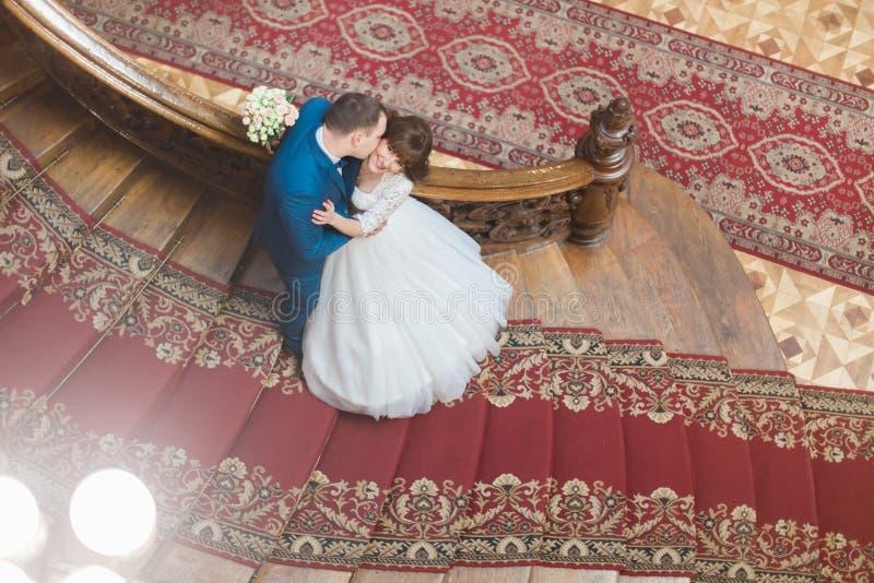 Щека красивого элегантного groom целуя красивой усмехаясь невесты на старых деревянных лестницах на богатой внутренней предпосылк стоковые изображения