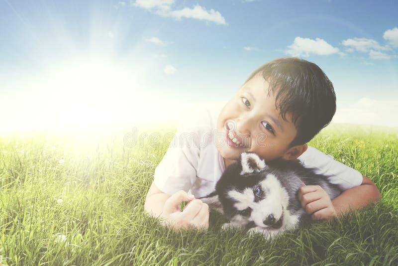 Щенок обнимать мальчика осиплый на луге стоковые изображения rf