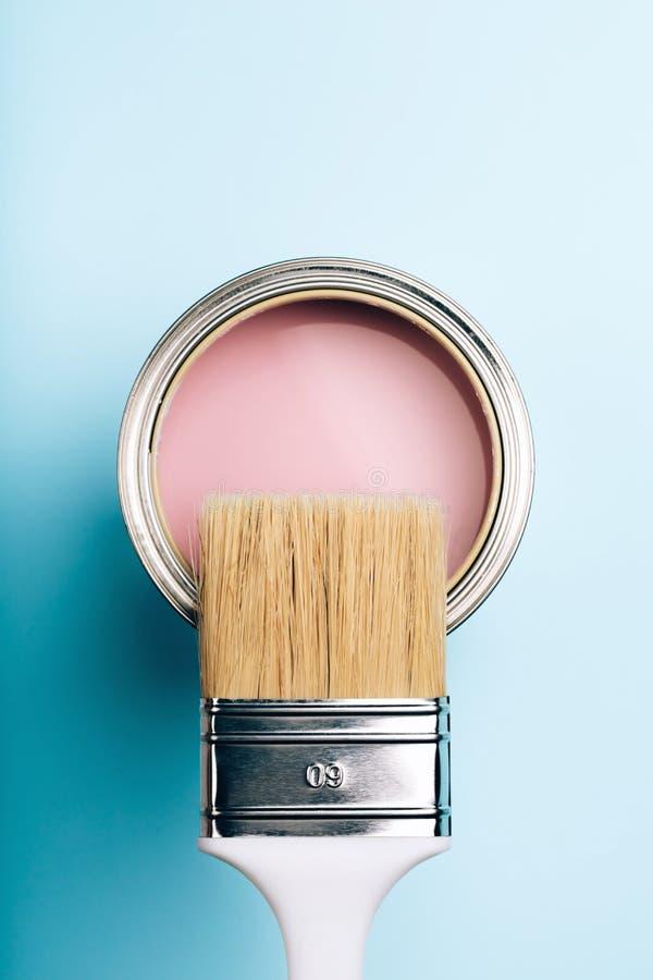 Щетка на открытой консервной банке розовой краски на голубой пастельной предпосылке стоковые изображения