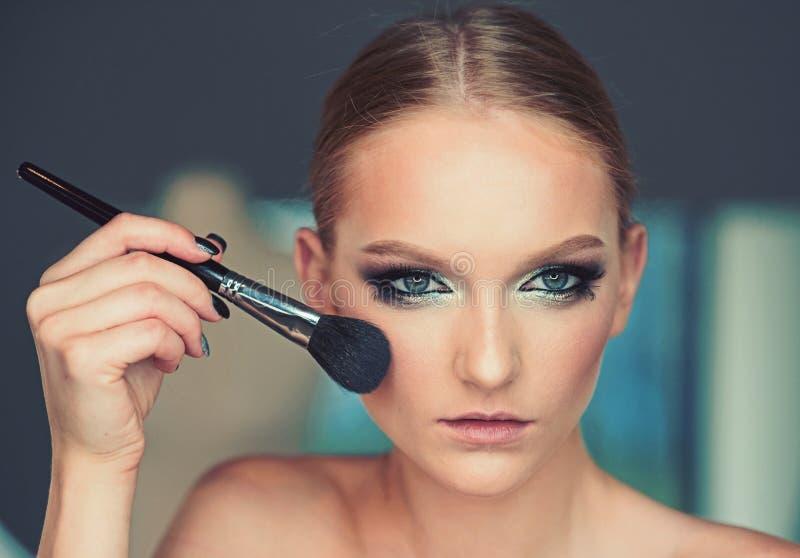 Щетка пользы женщины для состава, выражения лица Модель красоты прикладывает порошок на стороне, косметиках Женщина с молодой кож стоковое изображение