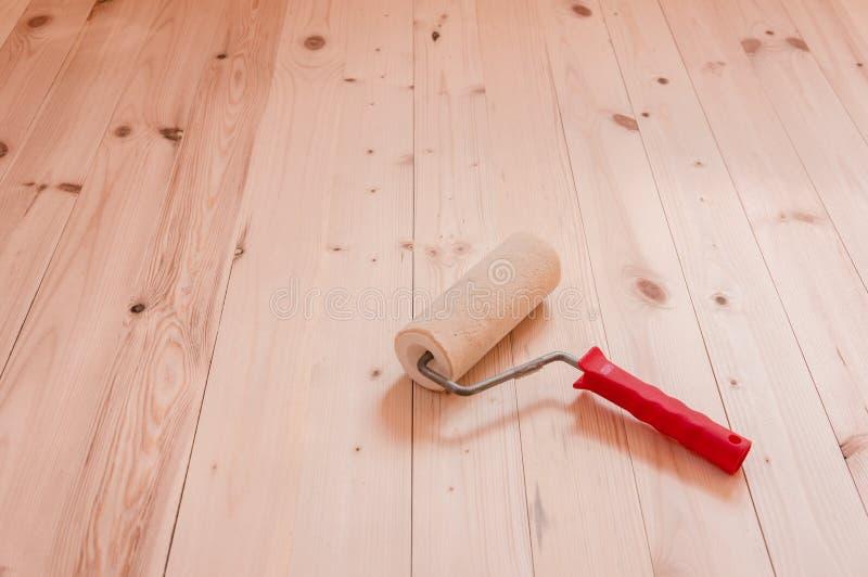 Щетка ролика краски на деревянной предпосылке стоковая фотография rf